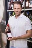 Stående av en le stilig visning en vinflaska Arkivfoton