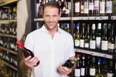 Stående av en le stilig visning en vinflaska Arkivfoto