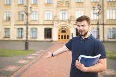 Stående av en le student med böcker och anteckningsböcker i hans händer som står på ingången till universitetet fotografering för bildbyråer