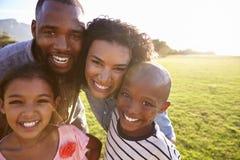 Stående av en le svart familj utomhus, tätt upp arkivbild