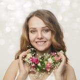 Stående av en le ung flicka i en halsband av rosor royaltyfri foto