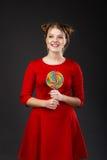 Stående av en le ung härlig flicka i en röd klänning med a Arkivfoto