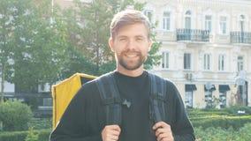 Stående av en le ung kurir med en gul påse i staden Skäggig grabb med en ryggsäck under gryningen leverans stock video