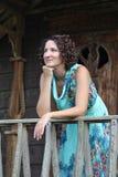 Stående av en le ung kvinna med mörkt lockigt kort hår Arkivfoto