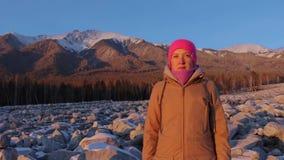 Stående av en le ung kvinna på foten av bergen på solnedgången lager videofilmer