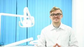 Stående av en le ung man för tandläkare i exponeringsglas på hans arbetsplats i den tand- kliniken Bära för Porthappy manligt tan arkivbilder