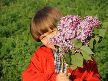 Stående av en le ung pojke med lilan i hans händer 1 Royaltyfria Foton