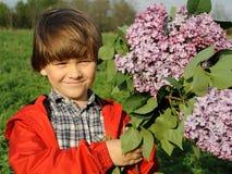 Stående av en le ung pojke med lilan i hans händer 1 Royaltyfri Bild