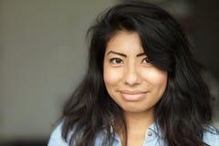 Stående av en le ung spansk kvinna Hon är lyckligt som isoleras på grå färger arkivfoto
