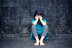 Stående av en ledsen asiatisk flicka mot grungeväggen Royaltyfri Foto
