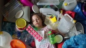 St?ende av en ledsen flicka som ligger i en h?g av plast- avfall Plast- ?r ett hot till milj?n, problemet av plast- stock video