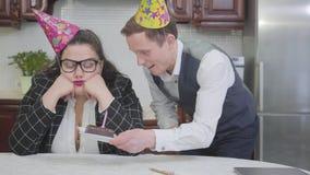Stående av en ledsen fyllig kvinna i födelsedaghatten i köket på tabellen Slank gullig man som lite sätter choklad stock video