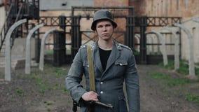 Stående av en ledsen tysk soldat som framme står av en koncentrationsläger Reenactmenten för andra världskrig stock video