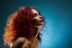 Stående av en lockig röd hårkvinna royaltyfri bild