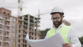 Stående av en lyckad ung tekniker eller arkitekt som bär en vit hjälm som ser i byggnadsritningarna i hans arkivfilmer