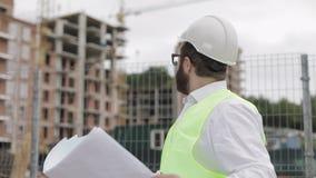 Stående av en lyckad ung tekniker eller arkitekt som bär en vit hjälm som ser i byggnadsritningarna i hans lager videofilmer