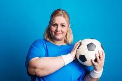 Stående av en lycklig överviktig kvinna med en boll i studio på en blå bakgrund fotografering för bildbyråer