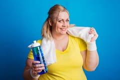 Stående av en lycklig överviktig kvinna med vattenflaskan i studio royaltyfria foton