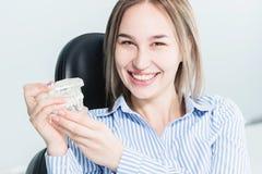 Stående av en lycklig attraktiv flicka i en tand- stol Skratta flickan på tandläkarens tidsbeställning med en käkemodell in arkivfoto