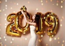 Stående av en lycklig förvånad kvinna som rymmer den närvarande asken på nytt års parti royaltyfri bild