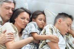 Stående av en lycklig familj som tillsammans sover i säng arkivbilder
