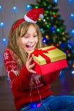 Stående av en lycklig flicka med en gåva på bakgrunden av en julgran Royaltyfria Bilder