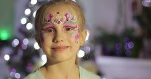 Stående av en lycklig flicka med ljus makeup på hennes framsida på bakgrunden av julgranen stock video