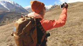 Stående av en lycklig flickahandelsresandefotograf i en hatt och solglasögon med en kamera runt om hans hals och en telefon i han arkivfilmer