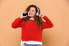 Stående av en lycklig gullig flicka som lyssnar till musik Royaltyfri Foto