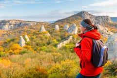 Stående av en lycklig handelsresande med en ryggsäck i beundra för berg arkivfoton