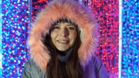Stående av en lycklig kvinna bredvid ljusen i gatan i aftonen arkivfilmer