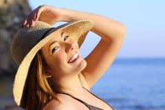 Stående av en lycklig kvinna med perfekt vitt leende på stranden Arkivfoto