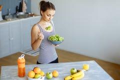 Stående av en lycklig kvinna som äter ett sunt mellanmål av nya frukt och grönsaker Banta och riktig näring fotografering för bildbyråer