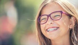 Stående av en lycklig le tonårs- flicka med tand- hänglsen och arkivbild