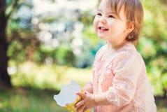 Stående av en lycklig litet barnflicka som spelar med ett stort leende arkivfoton