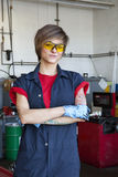 Stående av en lycklig mekaniker som bär det skyddande kugghjulet med armar som korsas i garage för auto reparation royaltyfri bild