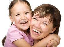 Stående av en lycklig moder som kramar henne dotter arkivfoton
