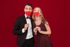 Stående av en lycklig parman och kvinna som rymmer pappers- hjärtor, på röd bakgrund, vändagbegrepp royaltyfria foton