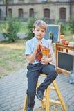 Stående av en lycklig skolapojke med blyertspennor Avsked Klocka Dag av kunskap Början av skolåret royaltyfria bilder