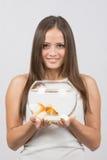 Stående av en lycklig ung flicka med ett akvarium med guldfisken i händer royaltyfri foto