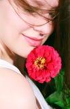 Stående av en lycklig ung kvinna med en blomma Fotografering för Bildbyråer