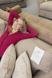 Stående av en lycklig ung kvinna med händer bak head koppla av på soffan i möblemanglager royaltyfri fotografi