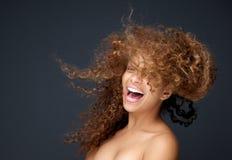 Stående av en lycklig ung kvinna som skrattar med att blåsa för hår Arkivbilder