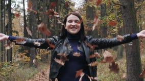 Stående av en lycklig ung kvinna som spelar med Autumn Leaves In Forest stock video