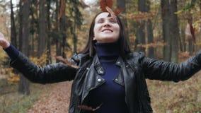 Stående av en lycklig ung kvinna som spelar med Autumn Leaves In Forest arkivfilmer