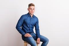 Stående av en lycklig ung man i en studio som sitter på en stol royaltyfri bild