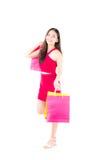 stående av en lycklig upphetsad asiatisk kvinna i rött klänninganseende och hållande shopping Royaltyfri Foto