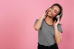 Stående av en lyssnande musik för gladlynt afrikansk kvinna med hörlurar royaltyfri foto