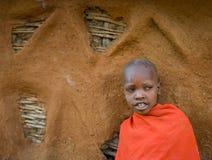 Stående av en Maasai pojke i traditionell klänning nära huset Royaltyfri Bild