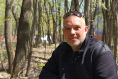 Stående av en man 35-40 år gammalt sammanträde framme av en skog I Arkivbild